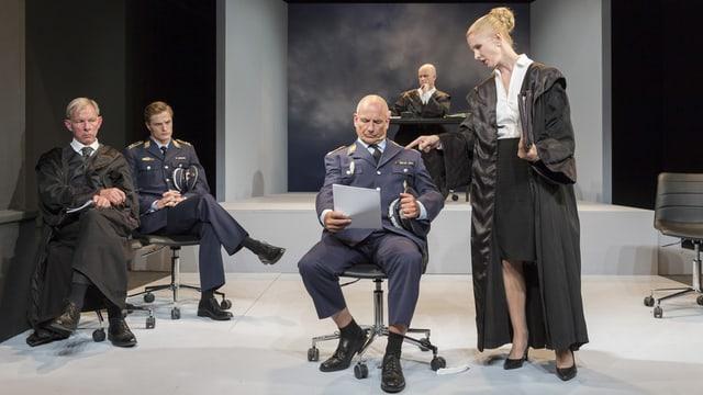 Theaterszene: Menschen in Talar und Uniformen auf einer Bühne.