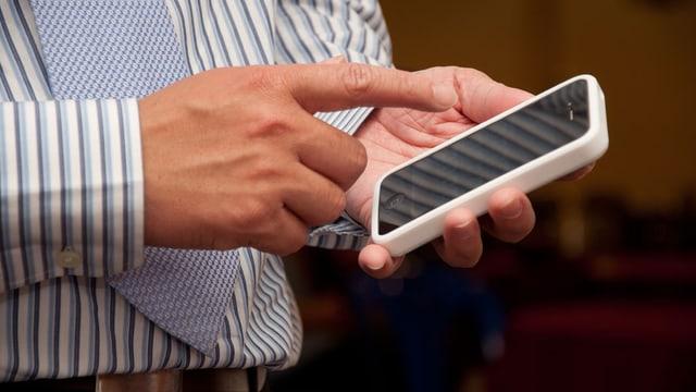 Ein Mann mit Krawatte tippt auf ein Smartphone