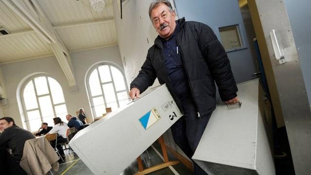 Zwei Urnen werden bei einer Abstimmung weggetragen