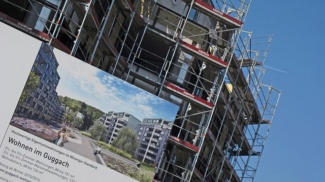 Das Verkaufsschild für Eigentumswohnungen, im Hintergrund das Gebäude im Rohbau