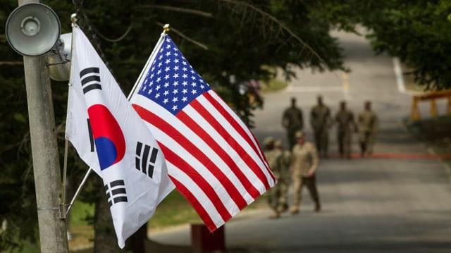 Südkoreanische und US-Flagge, Soldaten im Hintergrund