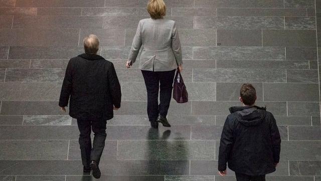 Die deutsche Bundeskanzlerin läuft einen Gang entlang.
