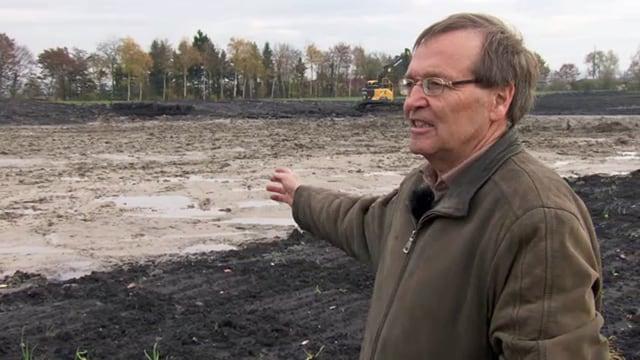Peter Thomet zeigt auf überschwemmten Acker.