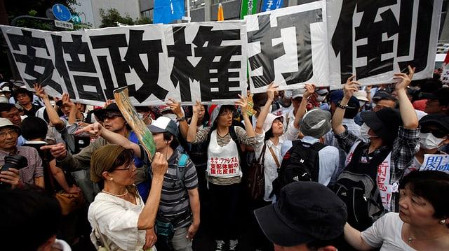 Japanische Demonstranten halten ein überlanges Transparent in die Höhe.