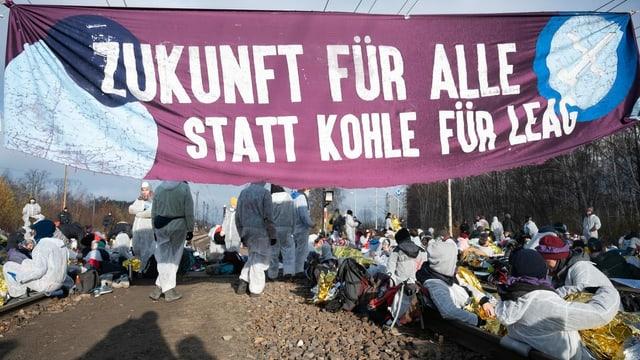 Demonstranten mit Banner besetzen Geleise.