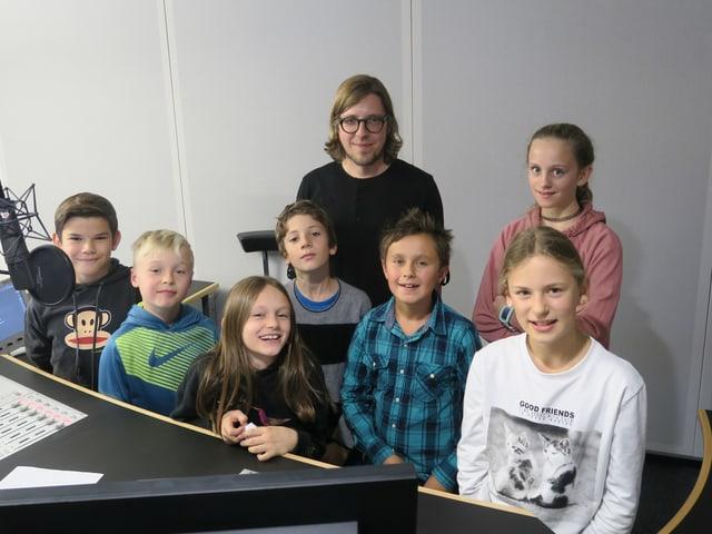 Sieben Kinder und ein Redaktor stehen hinter dem Sendepult im Radiostudio.