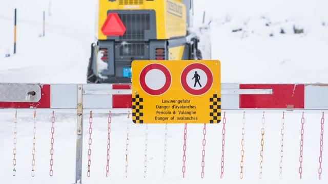 Lawinengefahr-Schild auf eingeschneiter Strasse