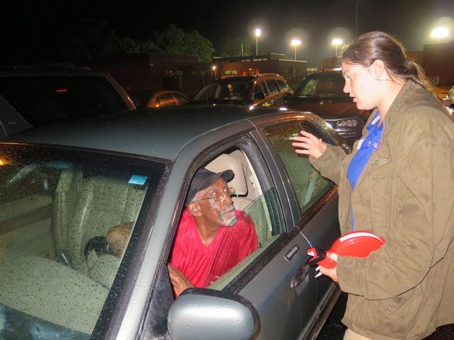Ein Mann im Auto wird von einer Freiwilligen über das Prozedere beraten.