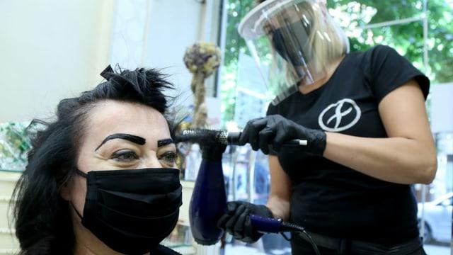 Frau lässt sich die Haare schneinen, mit Schutzmaske
