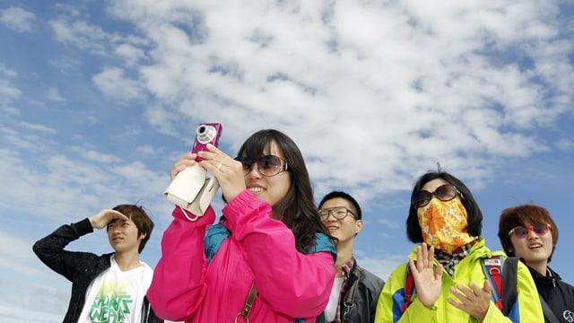 Gruppe von fünf asiatischen Touristen vor blauem Himmel mit ein paar Wolken, eine Frau macht ein Foto.