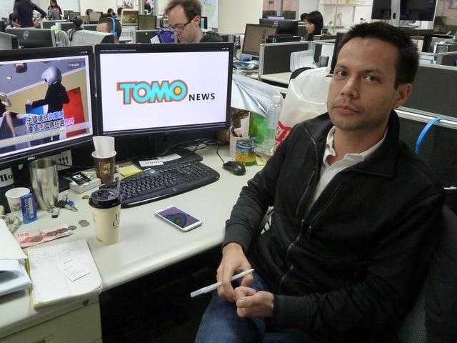 Ein Taiwanese sitzt vor seinem Computer in einem Grossraumbüro.