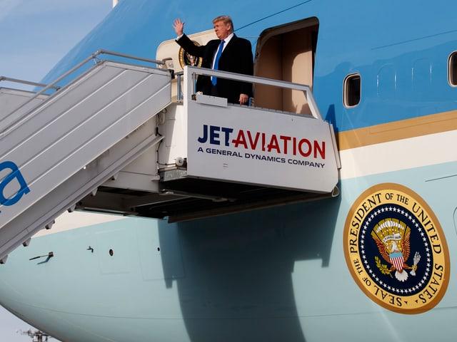 Trump steigt aus Flugzeug.