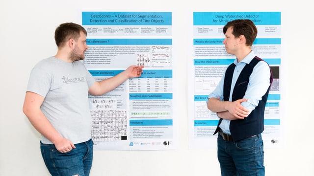 Zwei Männer stehen vor einem Plakat, das die Details zu den Forschungsergebnissen auflistet.