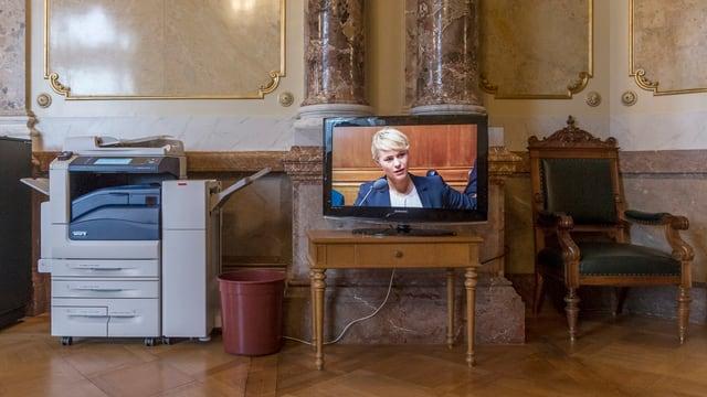 Wandelhalle in Bern. Auf einem Tisch steht ein Bildschirm. Darauf ist Nathalie Rickli zu sehen.