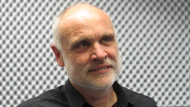 Martin Haug trägt kurzes graues Haar. Er ist im Radiostudio.