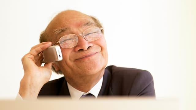 Alter Mann, telefonierend mit geschlossenen Augen und breitem Lächeln