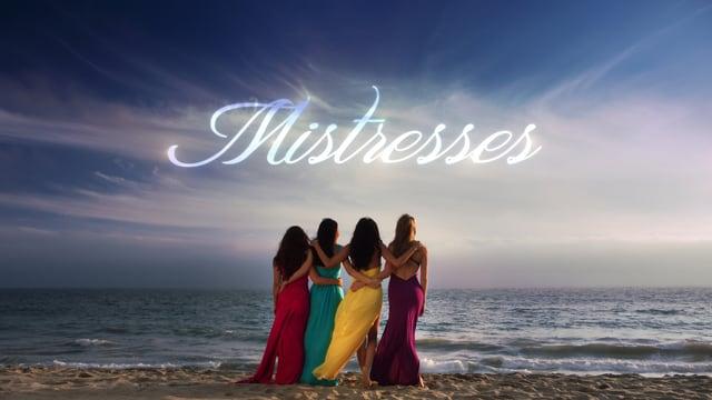 Vier Frauen in eleganter Abendkleidung stehen am Strand und blicken in Richtung Meer.