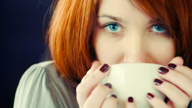 Rothaarige Frau hält mit beiden Händen eine Kaffeetasse am Mund und schaut den Betrachter direkt an.