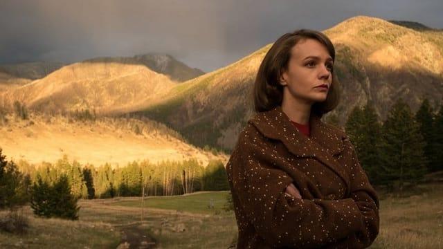Eine Frau steht vor einer hügeligen Landschaft