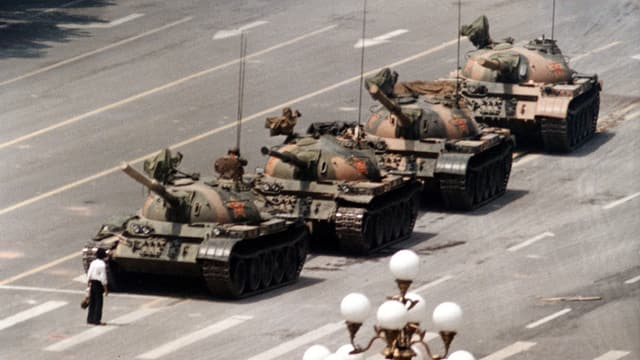Ein Mann mit Aktentasche stellt sich vier chinesischen Panzern entgegen.