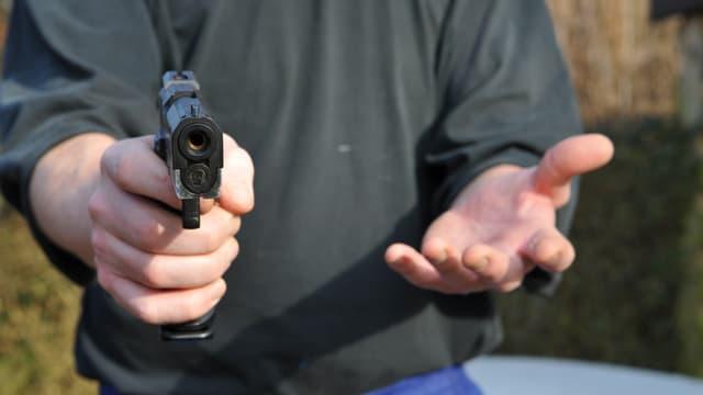 Mann droht mit einer Waffe.