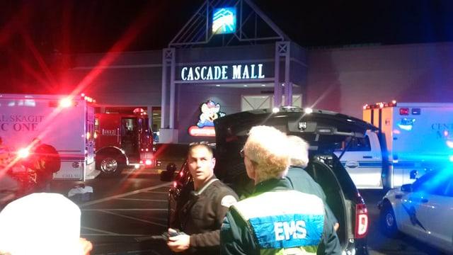 Rettungskräfte und Feuerwehrauto im Vordergrund, dahinter Eingang zum Einkaufzentrum
