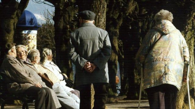 Ein altes Ehepaar von hinten, das in der Sonne spaziert.