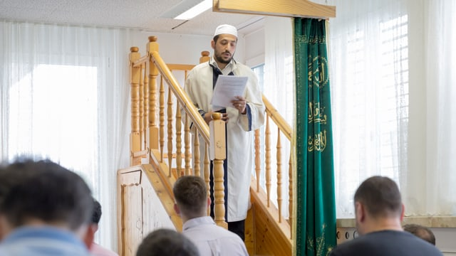 Imam betet vor einer Gruppe Männer