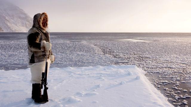Mann mit Gewehr steht am Rande des zugefrorenen Meeres