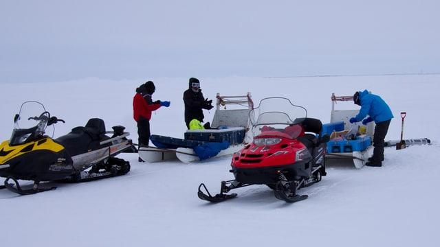 Die Forscher mit Schneemobilen und Material auf dem Eis.