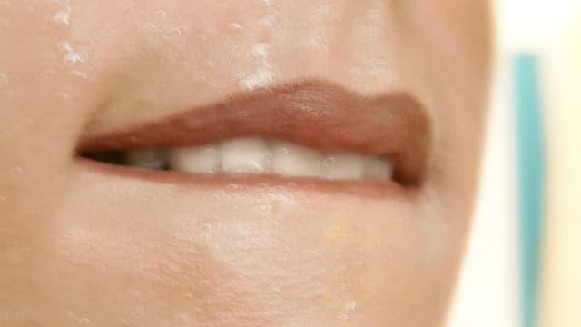 Eine Frau beisst sich mit den Zähnen auf ihre Unterlippe.
