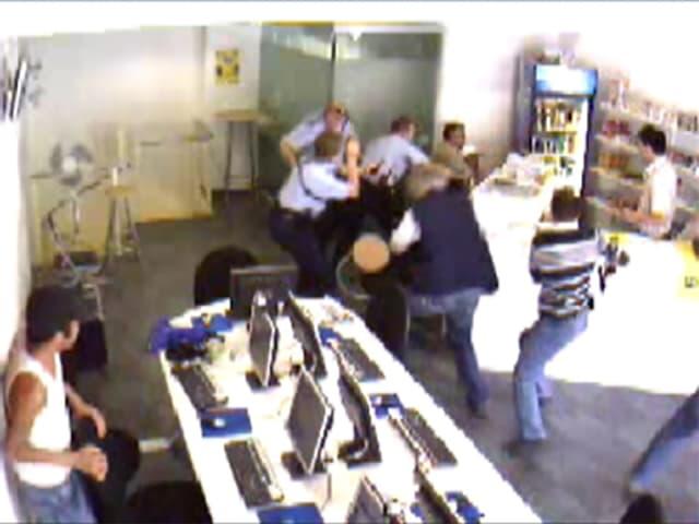 Blick in das Internet-Café, mehrere Beamte versuchen, dem Täter die Waffe zu entreissen.