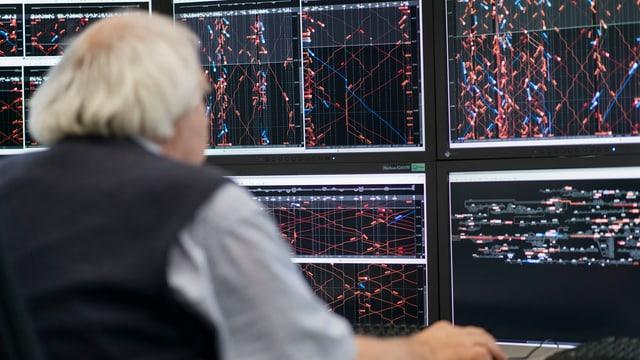 Ein Mann vor einem Bildschirm mit vielen Zügen