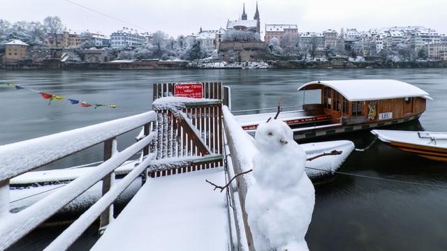 Verschneiter Steg bei der Münsterfähre. Auf dem Gelender hockt ein Schneemann.