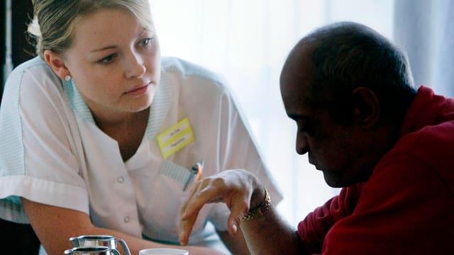 Eine Pflegerin kümmert sich um einen Demenzkranken