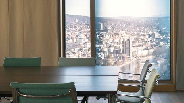 Ein Tisch mit Stühlen, dahinter aus dem Fenster die Aussicht auf Zürich.