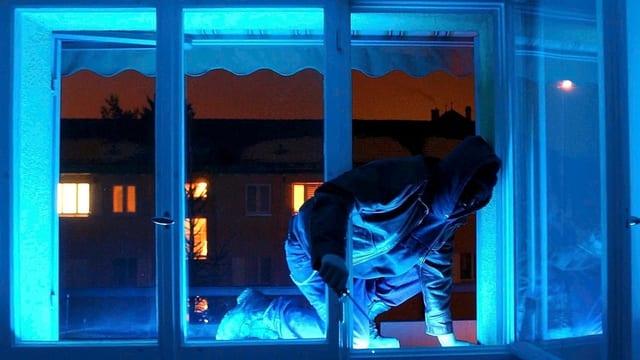 Einbrecher steigt bei Dunkelheit über ein Fenster in eine Wohnung ein