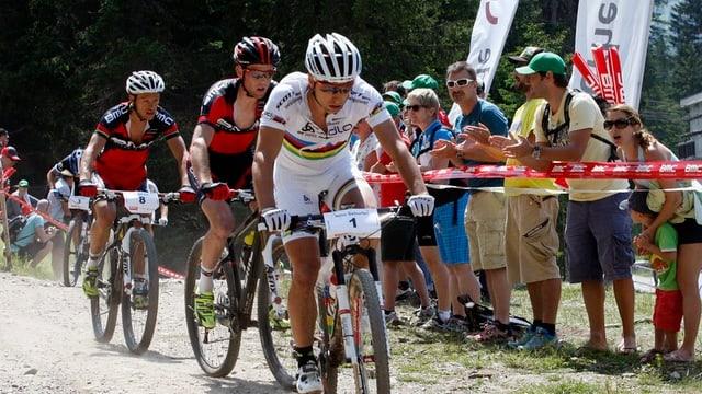 Drei Biker fahren hintereinander, Publikum feuert sie an.