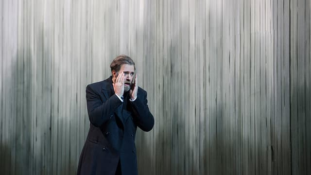 Mann mit erhobenen Händen vor grauer Wand