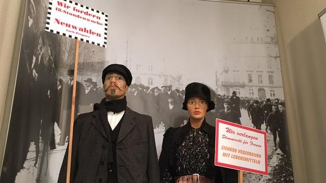 Zwei Puppen in Kleidern von 1918 mit Streiktafeln in den Händen.