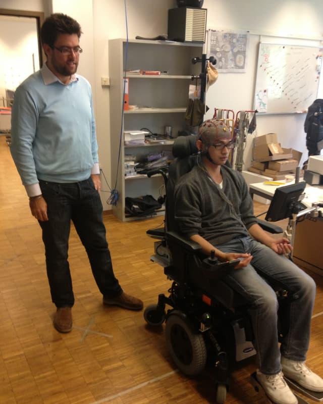 Alex Zhang versucht mit dem Rollstuhl zu fahren. Der Forscher steht dahinter.