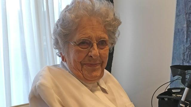 Eine ältere Frau mit Brille sitzt an einem Fenster in einem Wohnzimmer.