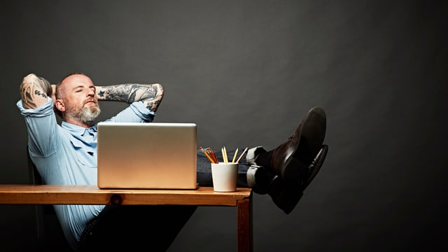 Ein Mann hängt auf einem Schreibtischstuhl und legt die Beine auf den Tisch.