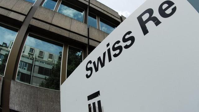Schwarzer Schiftzug und Logo der Swiss Re auf weisser Tafel vor einem Firmengebäude