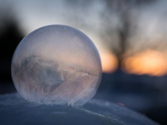 Eine gefrorene Seifenblase liegt auf einer Schneeschicht.
