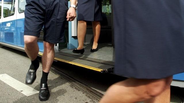 Ein Chaffeur in kurzen Hosen und eine Chaffeuse in Jupe verlassen ein Zürcher Tram
