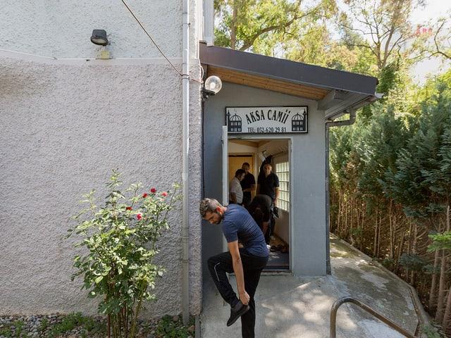 Ein Eingangsbereich eines Hauses mit grauen Wänden. Drinnen sind einige Männer zu sehen, vor der Türe zieht sich ein Mann die Schuhe an.