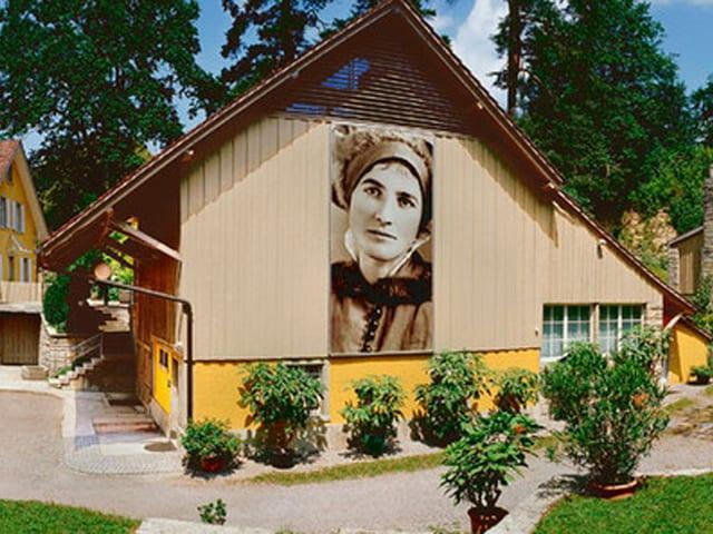 Gelbe Häuser, an einer Wand das Portrait einer Frau.