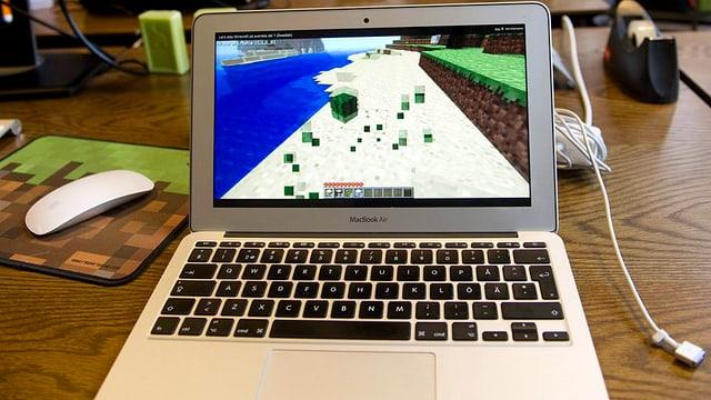 Notebook, auf dem Bildschirm ist die Minecraft-Klötzchenwelt erkennbar.