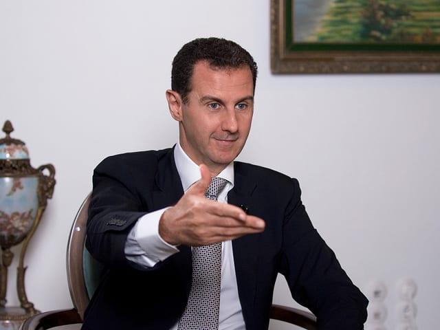 Bashar Al-Assad sitzt auf einem Stuhl und streckt die Hand aus